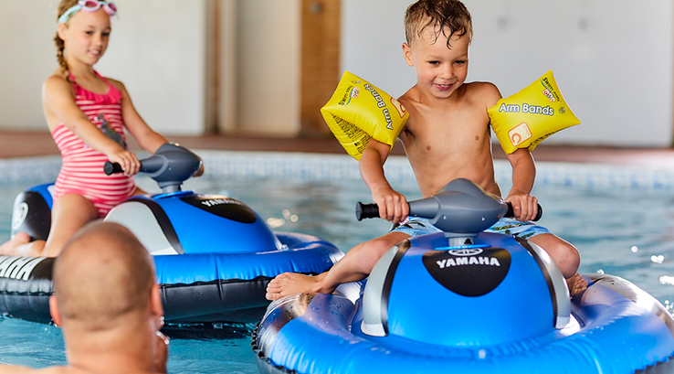 A boy using an inflatable jet ski in the indoor swimming pool