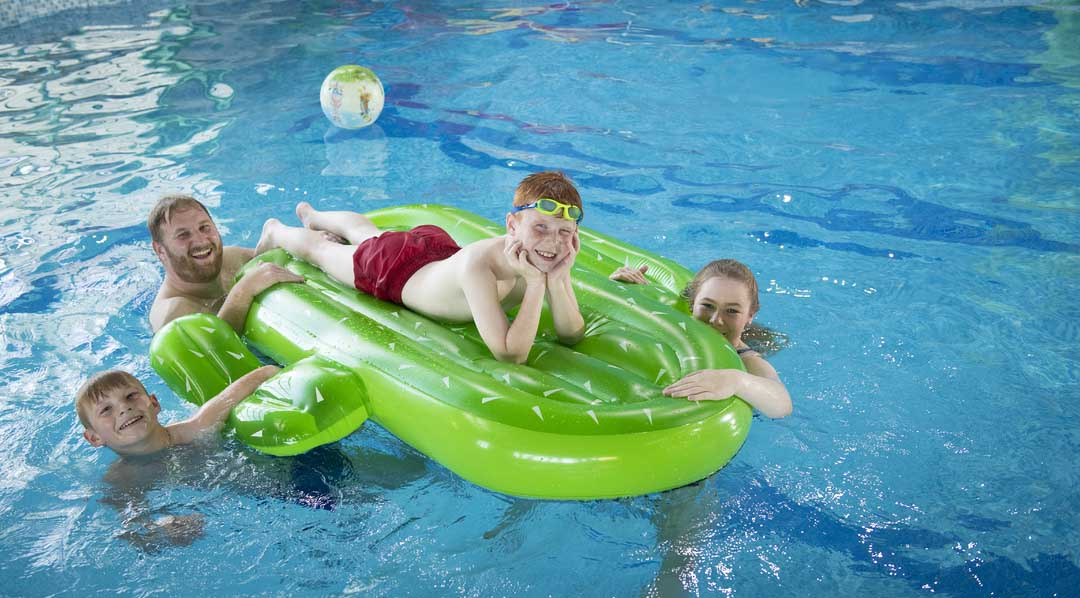 A family playing on an inflatable in the indoor swimming pool