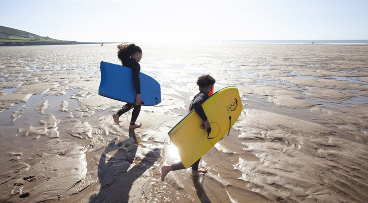 Two children running across Croyde Bay Beach with surfboards