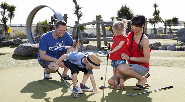 A family playing crazy golf at Trecco Bay Holiday Park