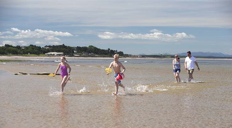 Family paddling in the shallows at Nairn Beach in Scotland