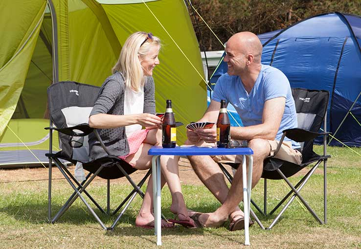 Couple relaxing outside their tent