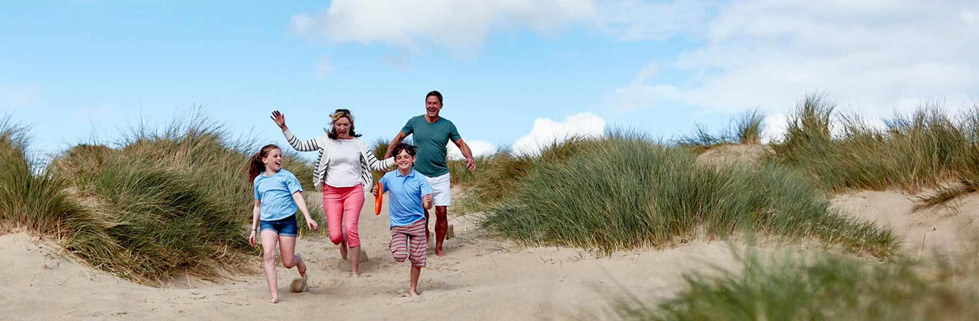 A family running to the beach through grassy sand dunes