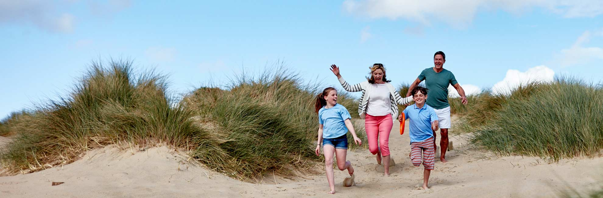 Family running thorugh sand dunes at camber sands
