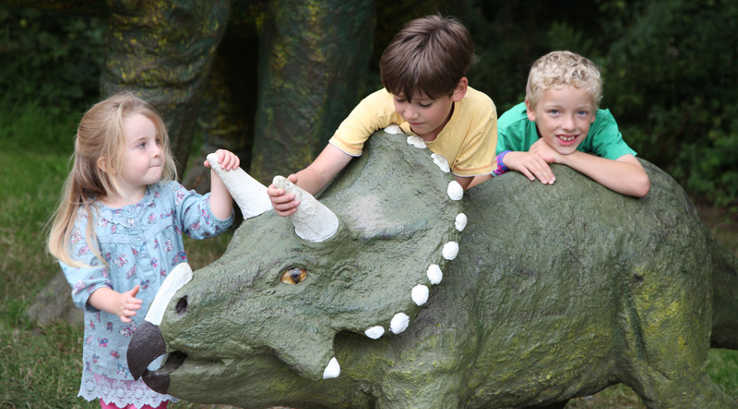 3 children with a model triceratops at Tenby Dinosaur Park