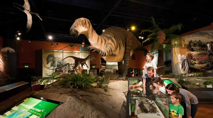 A group of children studying a dinosaur exhibit