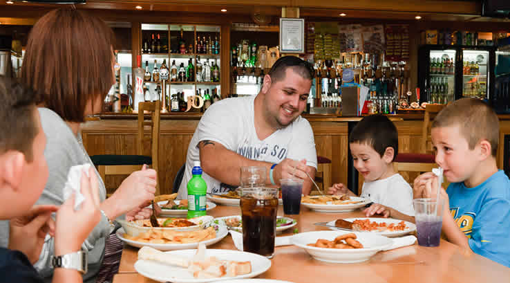 Family enjoying a meal at the Boathouse Tavern