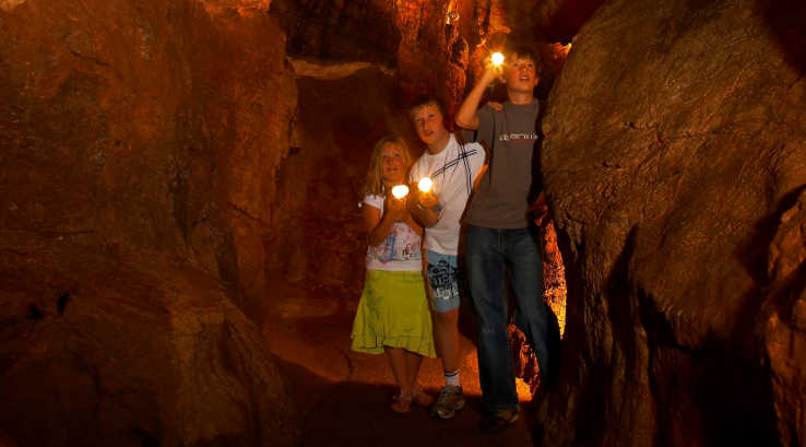 Children exploring Kent's Cavern by torchlight.