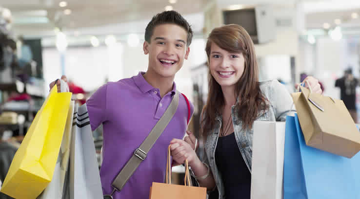 Young man and woman with lots of shopping bags