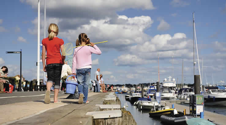 Children walking along the jetty at Poole Harbour