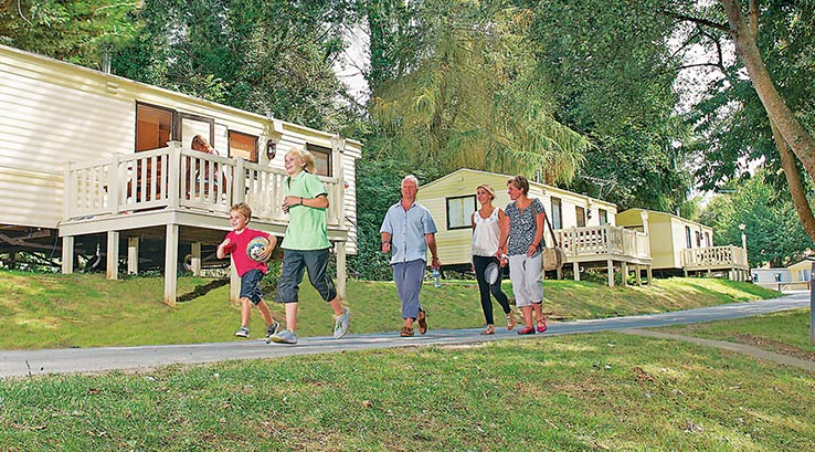 Family group walking past caravans.
