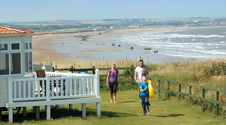 Family having fun outside their lodge. Beach in background..