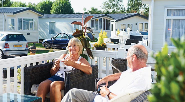 Couple relaxing in the sunshine on their veranda.