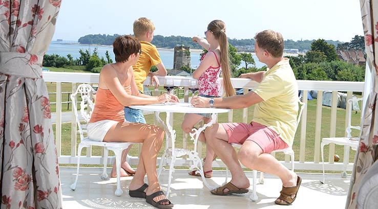 Parents and children on their lodge veranda, overlooking the seafront.