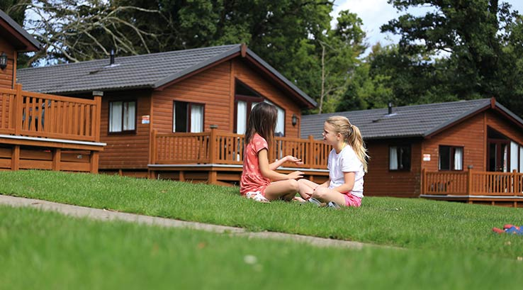 Two young girls chatting outside a lodge.
