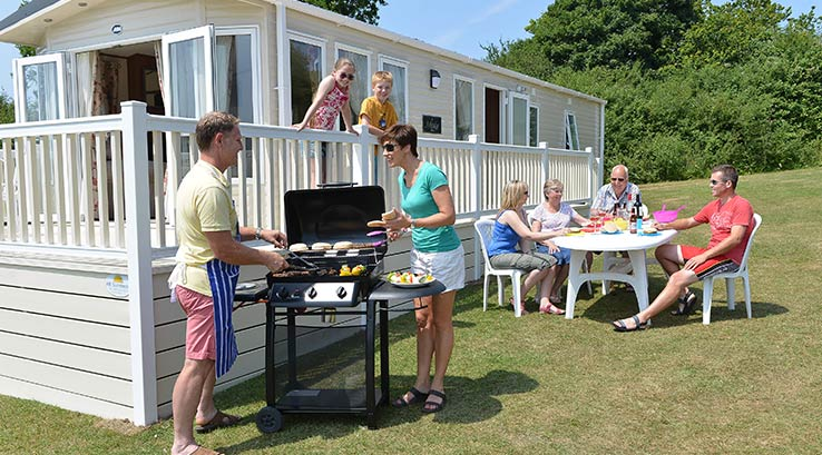 Family group enjoying barbecue outside their lodge.