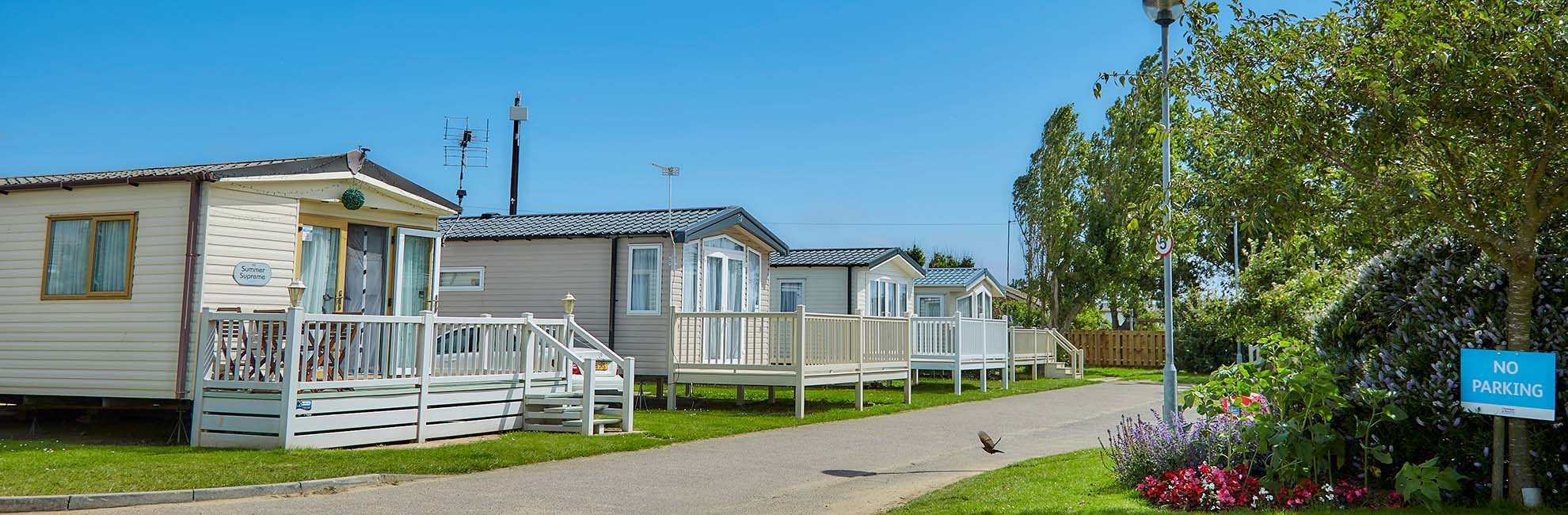 A family walking past the caravans at California Cliffs Holiday Park