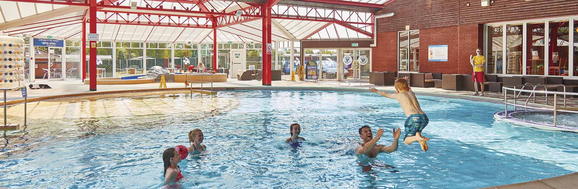 A family playing by the outdoor swimming pool at Cherry Tree Holiday Park in Great Yarmouth