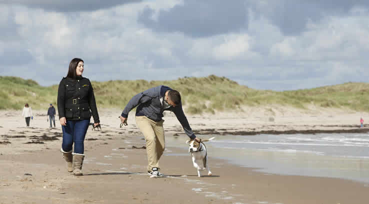 Couple walking their dog on Cresswell Beach.
