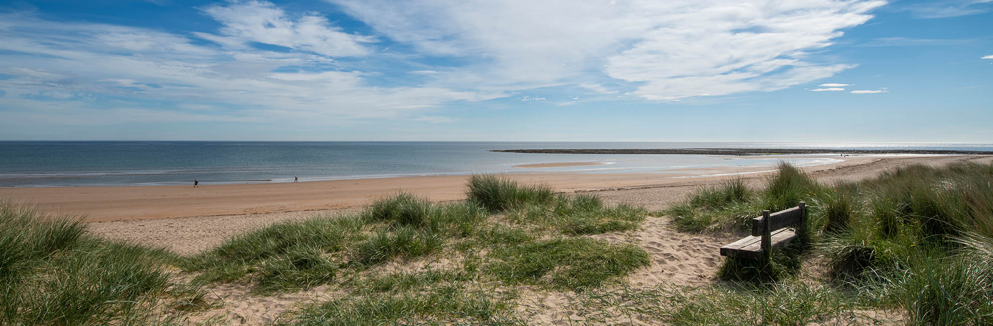A child running through the sand dunes at the beach near Cresswell Towers