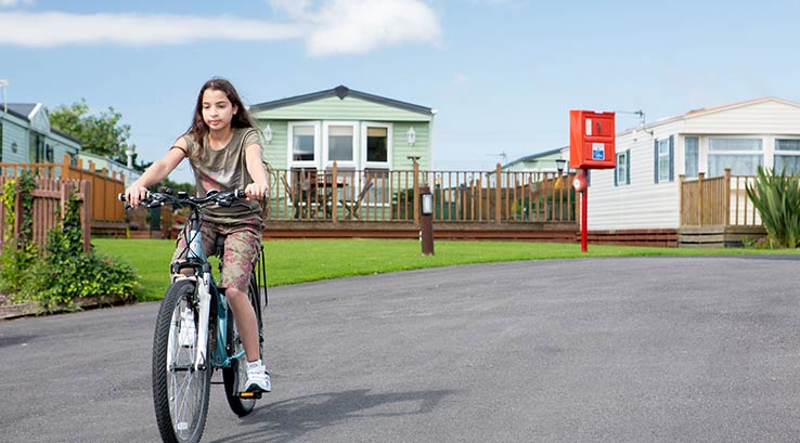 Girl cycling through the park grounds at Glasson Marina