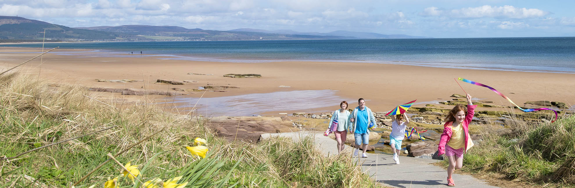 Family walking on to the beach at Grannie's Heilan' Hame