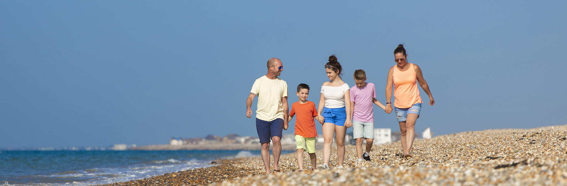 A family walking along the beach at Hayling Island