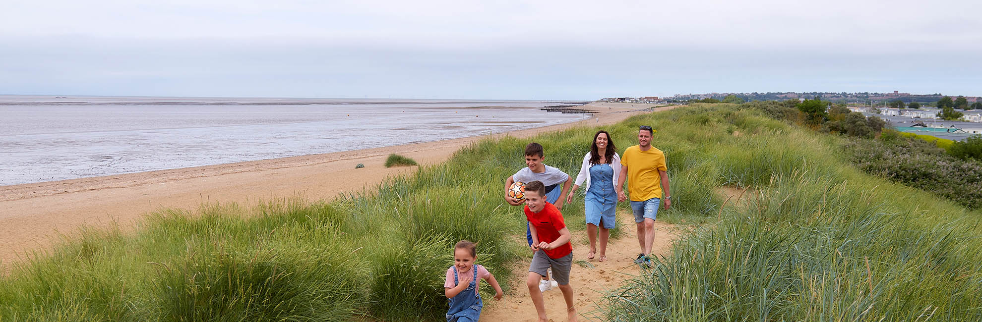 Little girl walking through the sand dunes at Heacham Beach