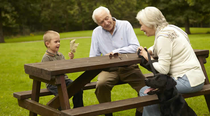 Grandparents, little boy and dog at a picnic table at Limefitt