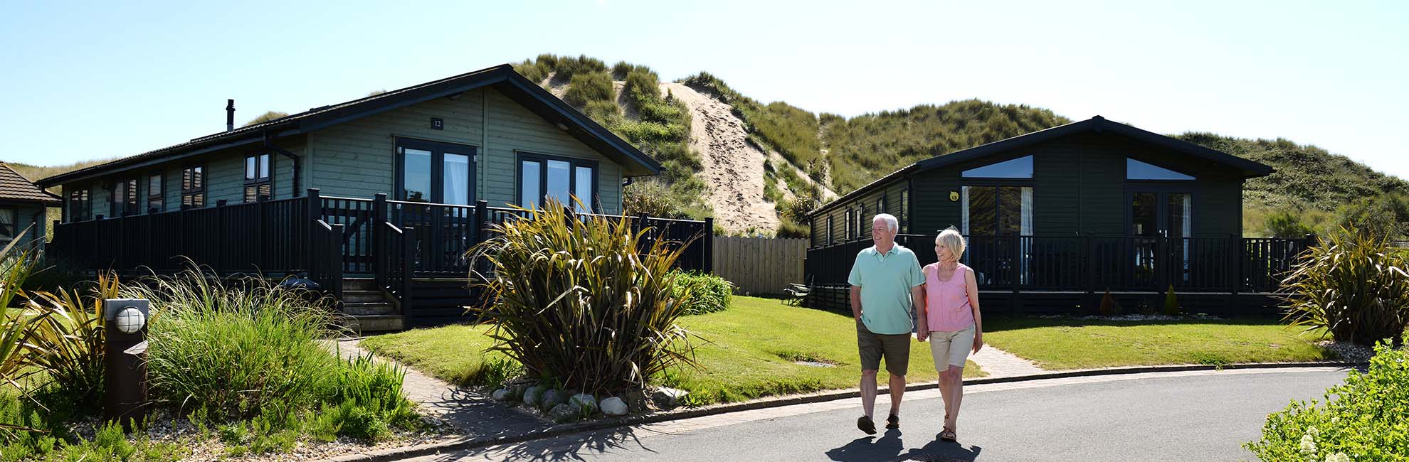 A couple strolling through the lodges at Ruda Holiday Park