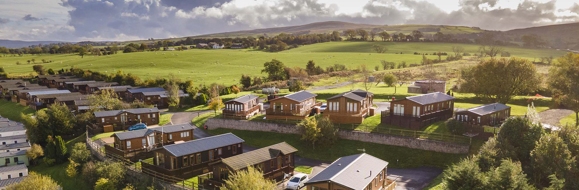 A view of wooden lodges at Todber Valley Holiday Park