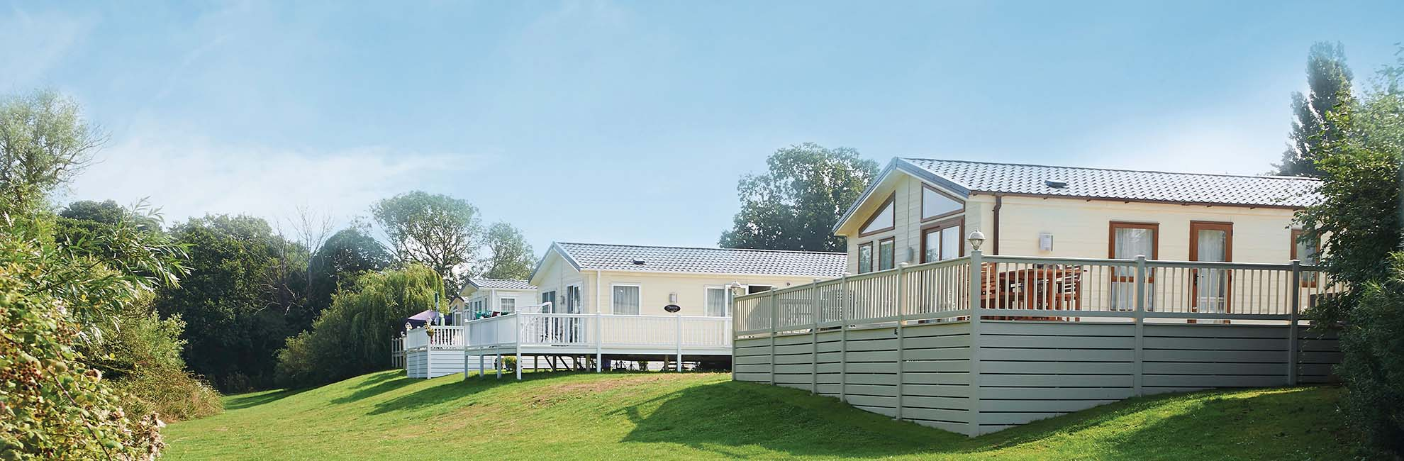 Caravans and lodges with verandas at Valley Farm Holiday Park