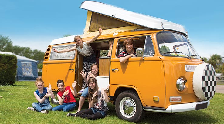 Teenagers spilling out of retro campervan