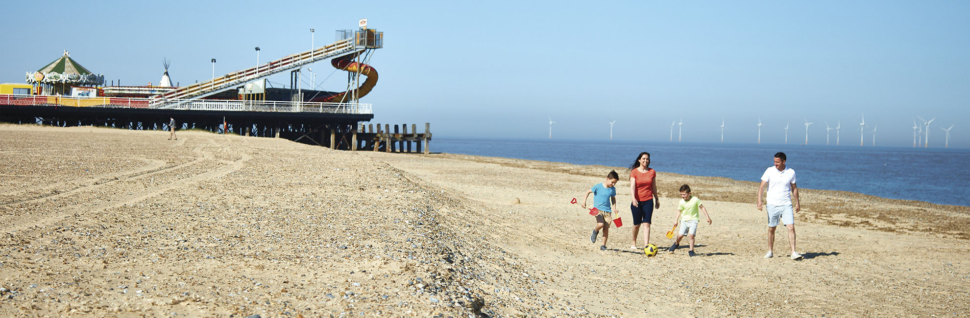 A family walking along the beach at Vauxhall Holiday Park