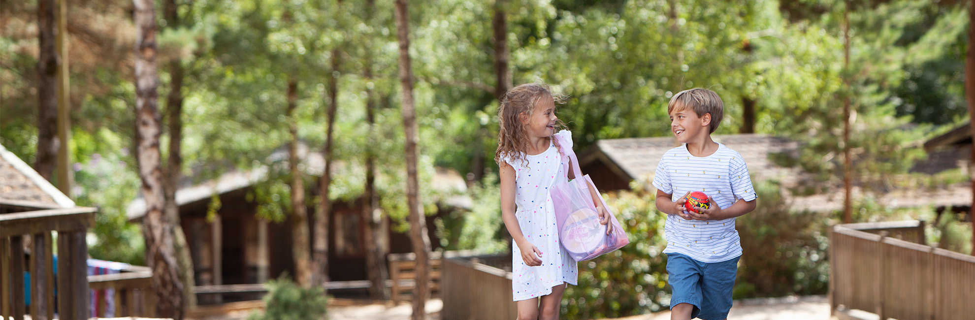 Two children walking through the lodges and trees at Warmwell Holiday Park