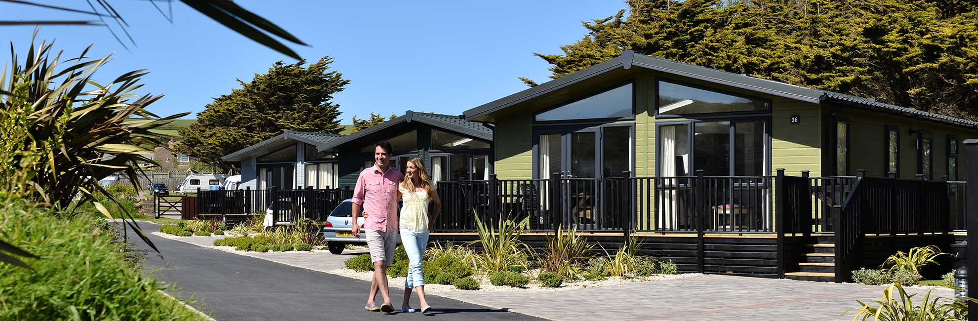 A couple walking past a row of luxury lodges at Ruda Holiday Park in Devon