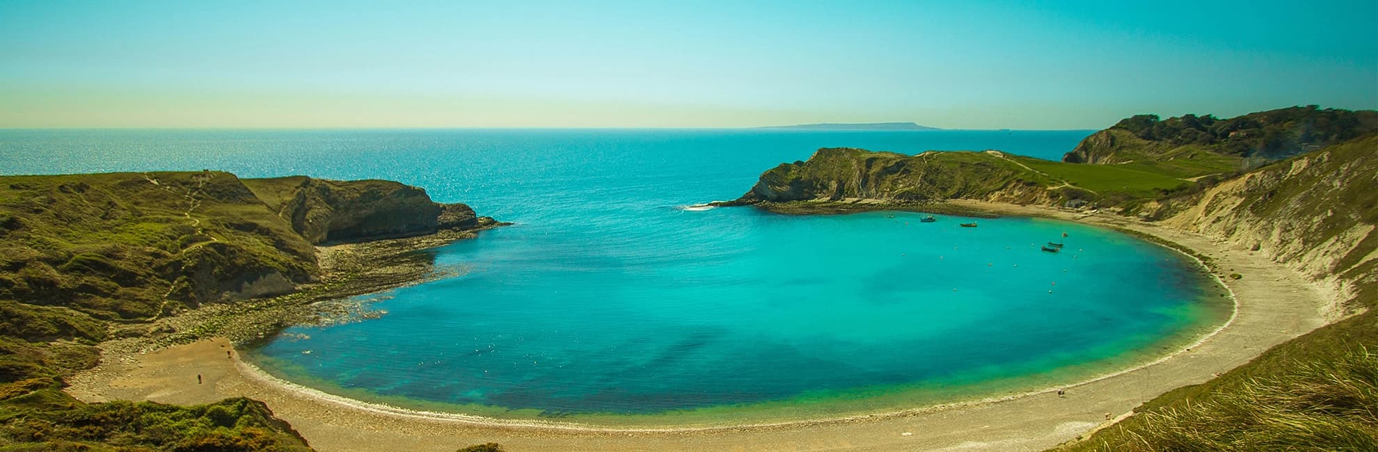 Looking out to see over the beautiful blue waters of Lulworth Cove in Dorset