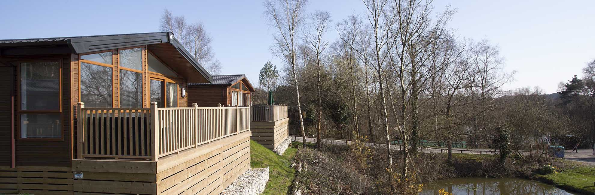 Two luxury lodges overlooking the fishing lake at Warmwell Holiday Park in Dorset