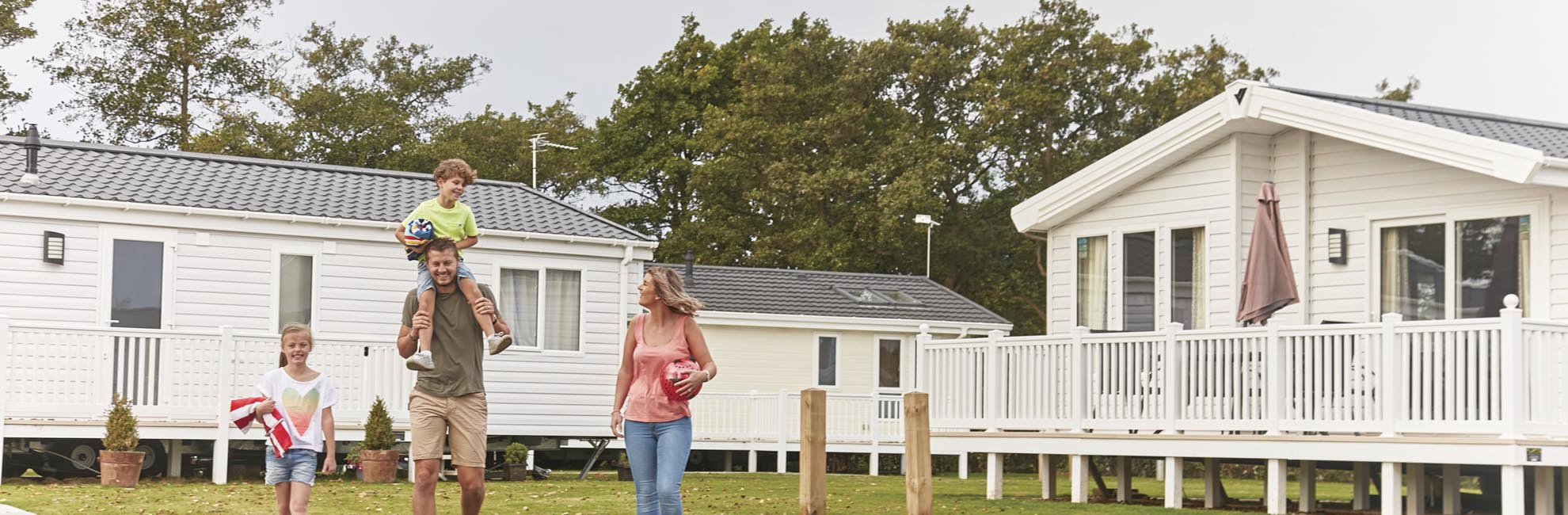 A family walking past their luxury lodge at Manor Park in Norfolk