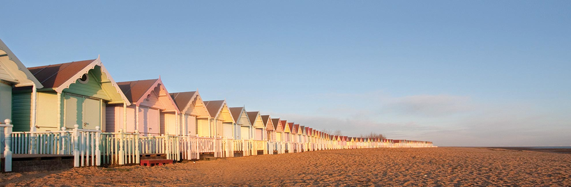 Colourful beach huts at sunrise on an Essex beach
