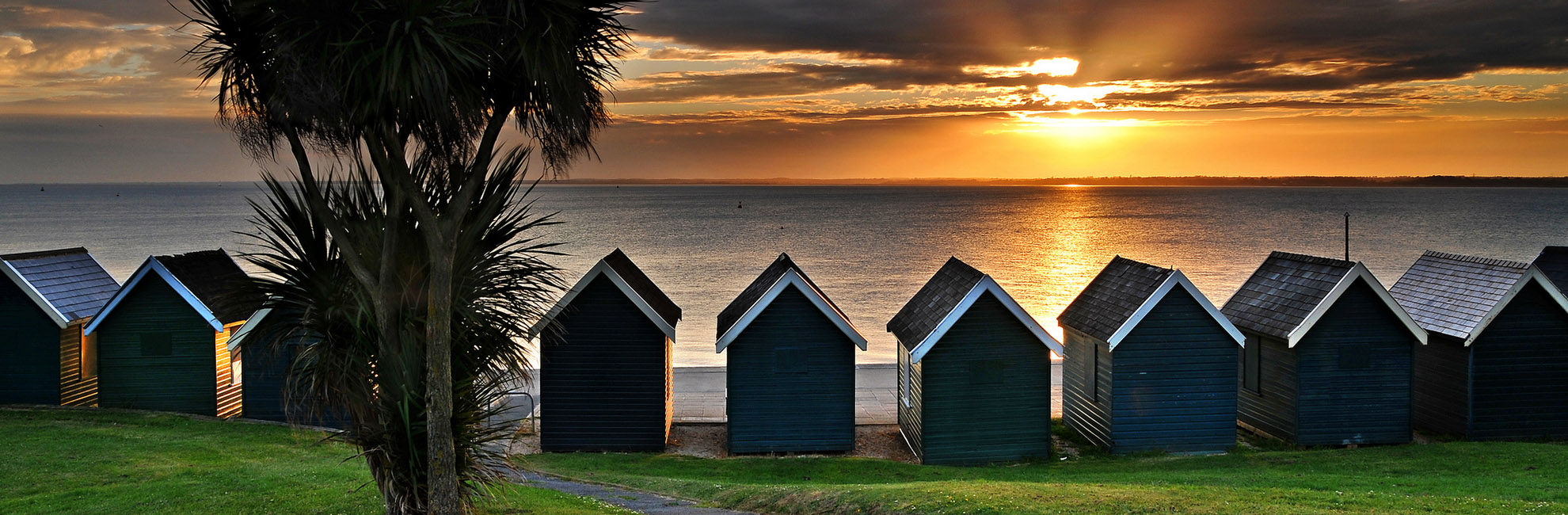 Beach huts overlooking a sunset over the sea