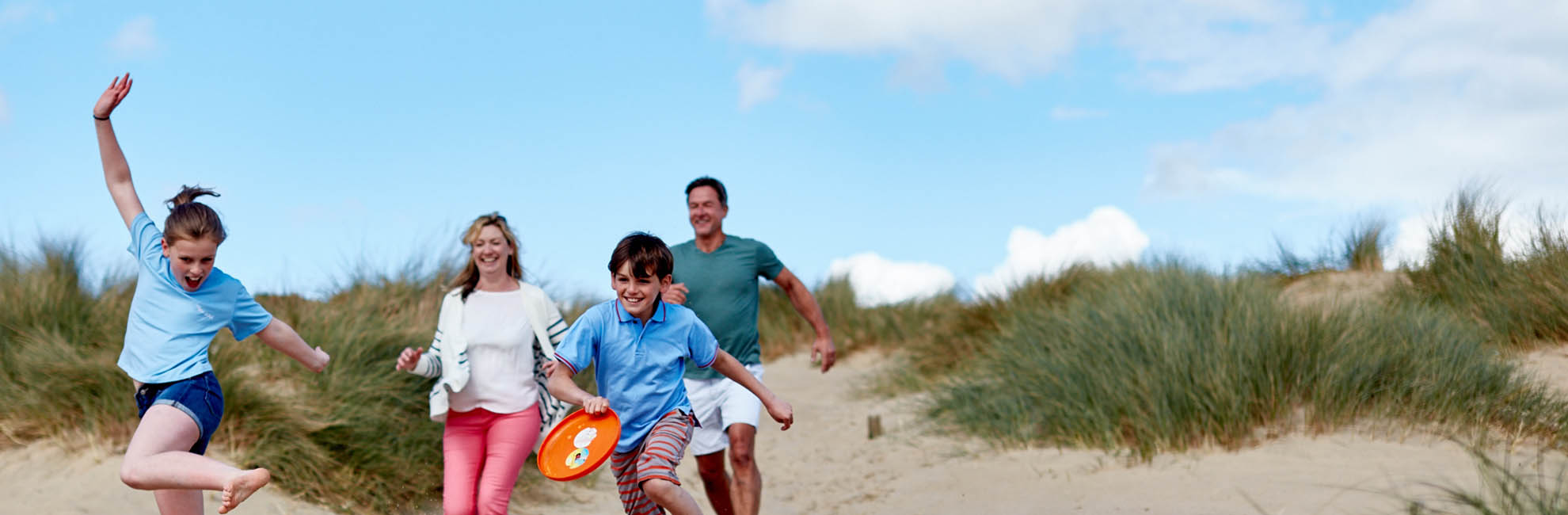 A family running through the grassy dunes towards Camber Sands Beach in Sussex