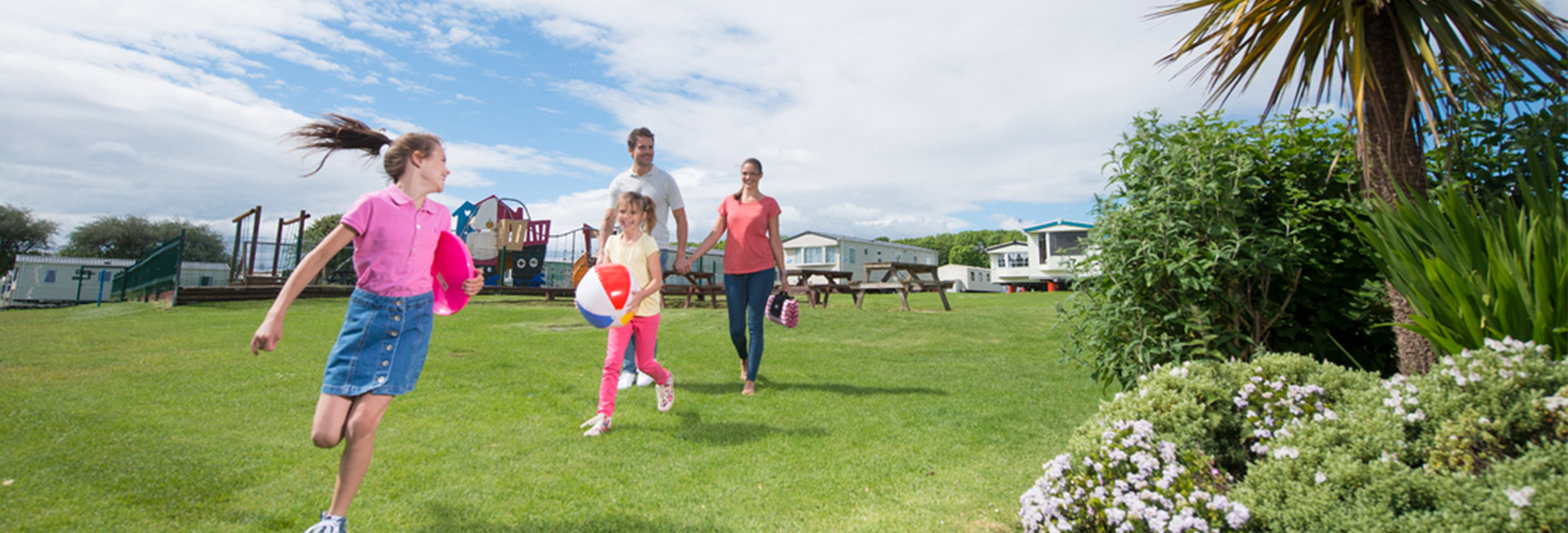 A family running across the grass of a caravan park