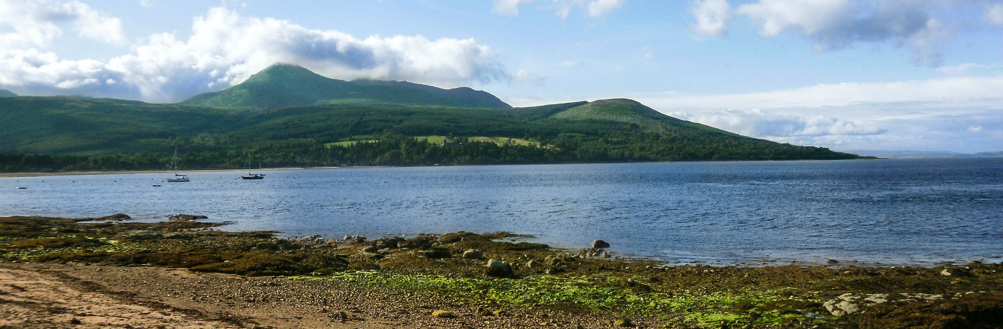 A peaceful bay surrounded by green mountains and hillside on the Isle of Arran in Scotland