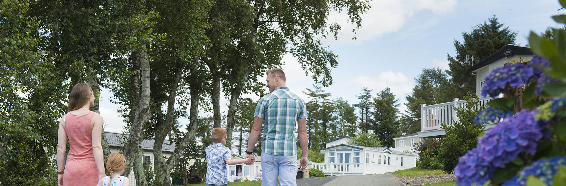 A family walking towards their lodge on a Parkdean Resorts Holiday Park in Wales