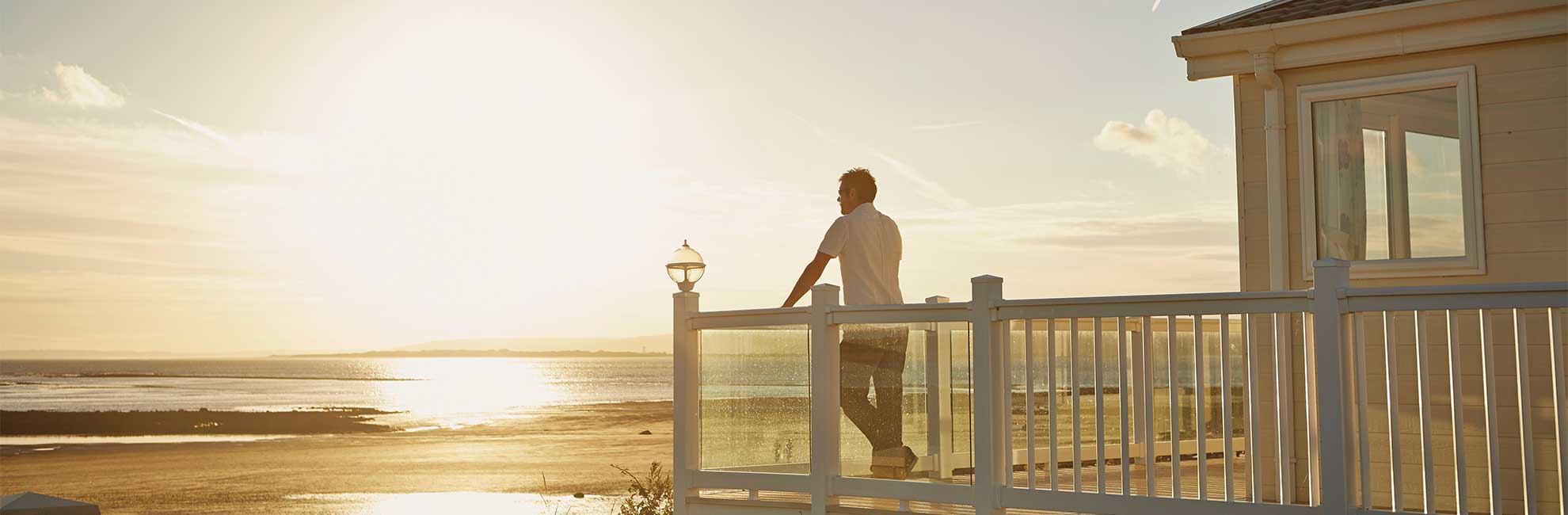 A man enjoying the sunset over the sea from his lodge veranda