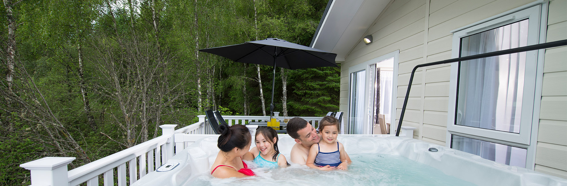 A family enjoying the hot tub of their lodge