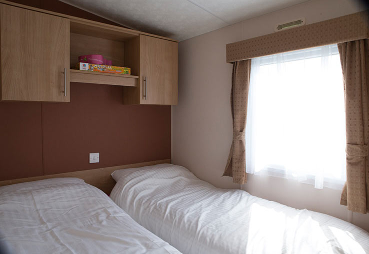 This three bed model can comfortably sleep up to eight, thanks to additional sleeping in the lounge. There's also double glazing and central heating to keep everyone cosy.